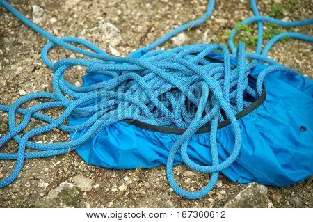 Close up A twisted blue rope climbing rope lying on the ground at the foot of the cliff
