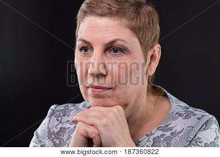 Portrait of sitting old woman looking side on black background