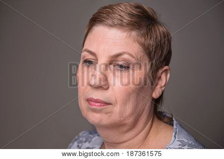 Portrait of old woman looking down on white background