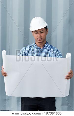 Engineer Looking At Blueprints In Construction Site