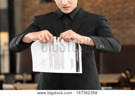 Angry businessman tearing agreement in pieces .