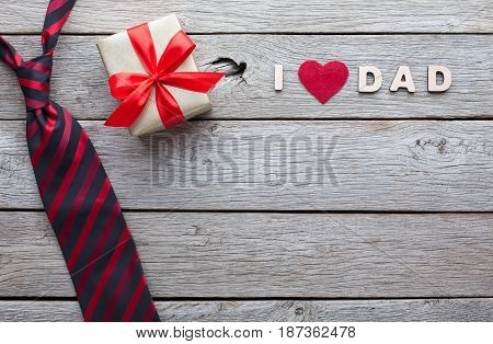 Happy Fathers Day card with male presents, love dad letters, watch and other man things on rustic wood background