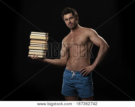 Knowledge is power concept strong muscular man holding stack of books