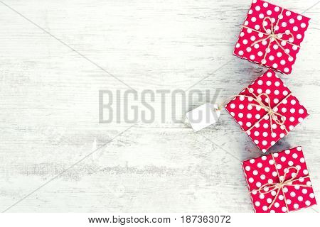Empty card tied over red dotted gift box. Red dotted gift boxes over white wood background. Copy space.