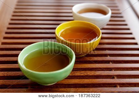 Coloful pialas or teacups with tea on wooden teabord for traditional Chinese tea ceremony, selective focus