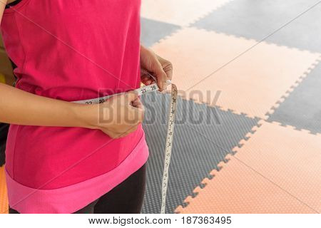 sport pink shirt woman with measuring tape on a slender her waist