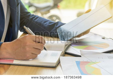 businessman writes business plan with tablet with soft light effect selective focus