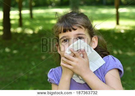 Young girl with allergy symptom blowing her nose