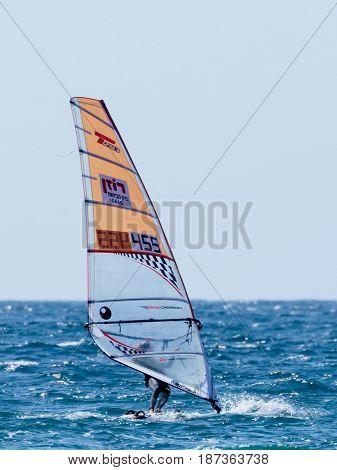 Nahariya Israel - January 07 2016 : Young athlete in a color tracksuit exercising in windsurfing in the Mediterranean sea in Nahariya Israel