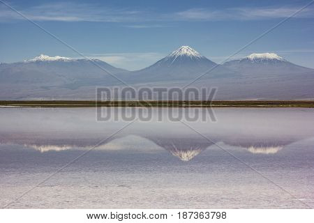 mirror surface of salt mountain lake surrounded by high peaks in atacama desert in Chile with blue sky