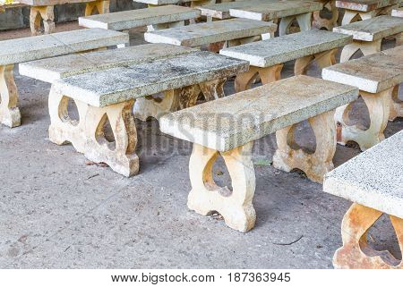 Closeup To Many Dirty Cement Benches In Quiet Place