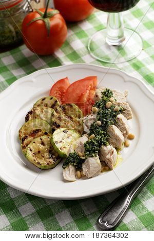 Chicken breast with Pesto sauce, roasted summer squash, and sliced tomato