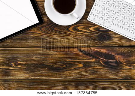 Office desk with copy space. Digital devices wireless keyboard mouse and tablet computer with empty screen on burned wooden table with cup of coffee top view