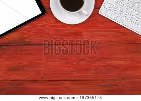 Office desk with copy space. Digital devices wireless keyboard mouse and tablet computer with empty screen on red wooden table with cup of coffee top view
