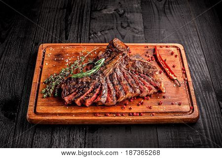 Sliced medium rare grilled steak on rustic cutting board with rosemary and spices , dark rustic wooden background, top view, place for text