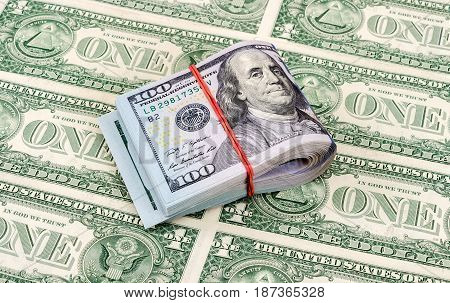 Folded american dollar bills wrapped by rubber band over dollars background