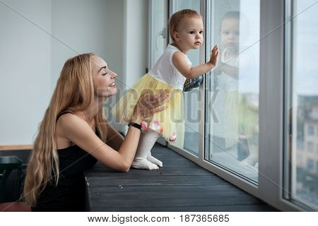 Mom and daughter are standing near the window. Girl looks out the window with her hands pressed