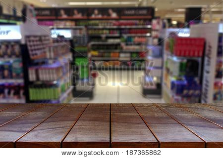 Empty wooden table space platform and blurred Supermarket aisle with product shelves background for product display. montage