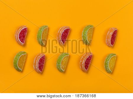 Still life of colored lobules of marmalade lying in two rows on an orange background