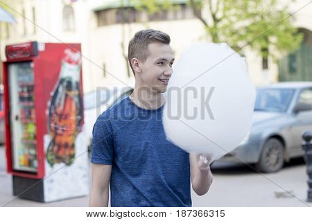 NIZHNY NOVGOROD, RUSSIA  May 20, 2017: Night of museums festival.The young man does try, advertises and sells cotton candy. NIZHNY NOVGOROD