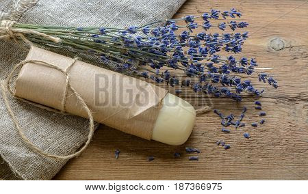 Lavender soap bar with a bouquet of lavender on a wooden background with