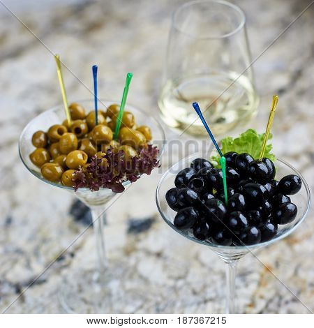 Appetizer. Green and black olives served in martini glasses with glass of white wine on marble table