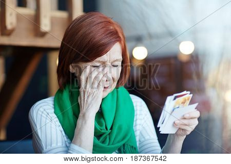 Aged woman wiping tear while looking through pictures of her family
