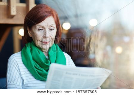 Modern senior woman with newspaper reading latest news