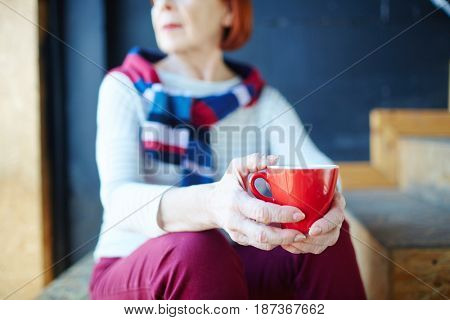 Red mug with hot drink in hands of relaxed senior woman