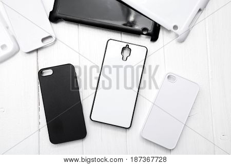 Different monochrome black and white cases for cellphones on the table, topshot