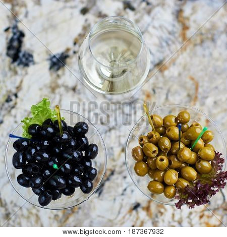 Appetizer. Green and black olives served in martini glasses with glass of white wine on marble table. Top view or flat lay.