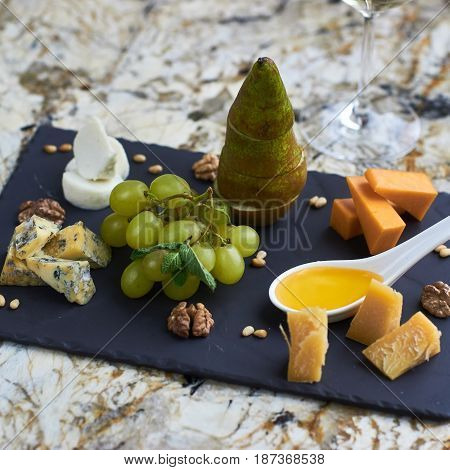 Cheese plate with fresh fruits served on black ceramic board on marble table