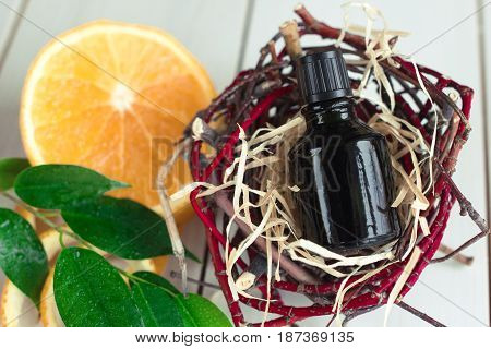 Brown bottle with essential oil in decorative nest on wooden table.