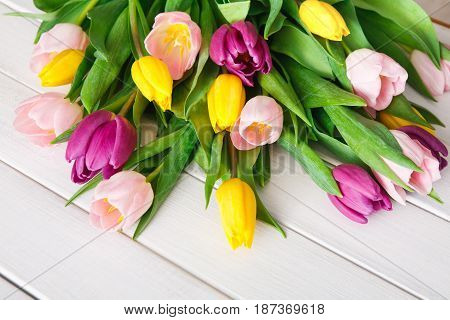 Colorful tulips on white wood background, copy space. Bouquet of flowers. Mothers day greeting card mockup.