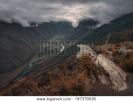 Mountain valley along the mountain river under a gloomy low sky covering the tops of the mountains