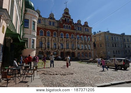VYBORG, RUSSIA - JUNE 6, 2015: People on the square against old Town Hall and monument to Torgils Knutsson, the founder of Vyborg castle. The monument was erected in 1908, reconstructed in 1993