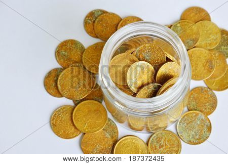 gold coin in glass bottle on white background