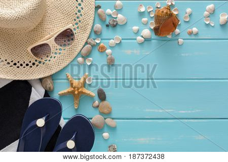 Vacation background on blue wood, top view with copy space. Beach accessories, flip flops and seashells