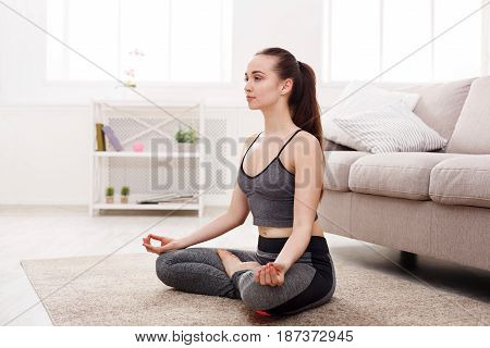 Yoga at home, woman in meditation lotus pose. Young girl relax exercise