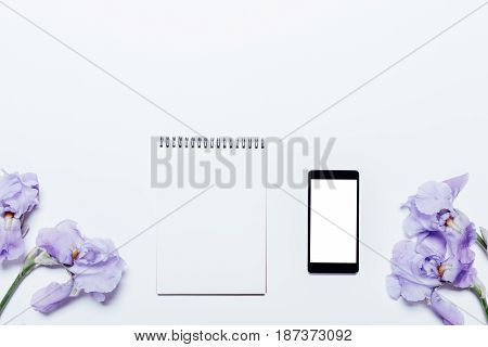Blue Flowers, Mobile Phone And Notepad Lie On A White Background