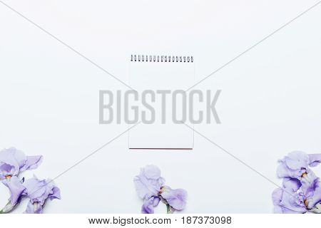 Blue Flowers And A Notepad Lying On A White Background