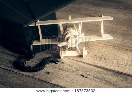Wood Toy Airplane With Graduation Cap On Wood Table.