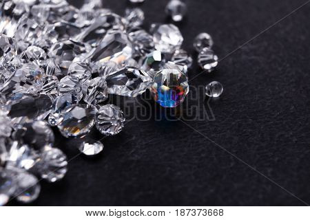 Beautiful diamonds on black background, free space. Pile of shiny crystals close-up. Jewelry, luxury, treasure concept