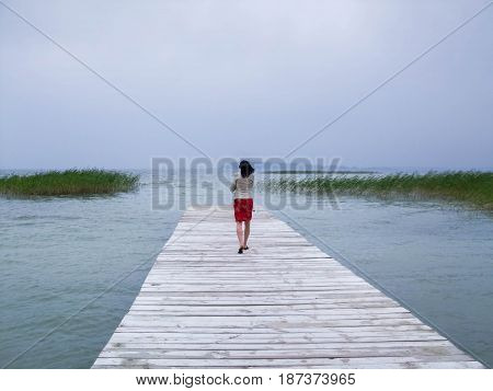 Lonely Girl On The Pier. One Girl On The Bridge. One Girl In The Distance.