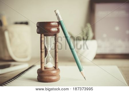 Hourglass With Pencil On Notebook , Time Passing Concept .