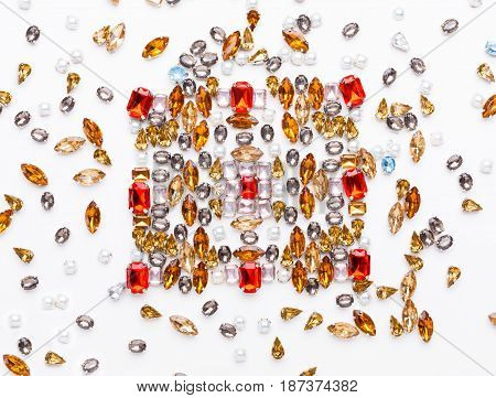 Beautiful ornament of gemstones on white background. White, pink, red and yellow crystals pattern. Jewelry kaleidoscope design, messy workplace