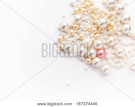 Pile of colorful pearls on white background. Nacreous beads closeup. Female accessories, bijuterie, needlework concept