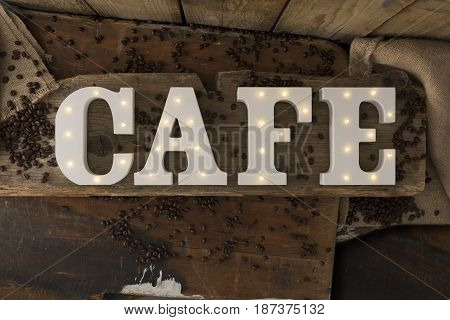 Illuminated Letters Spelling Cafe With Coffee Beans On Wooden Surface