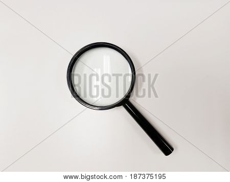 Magnifying glass isolated on white vackground reflected ceiling electronic light