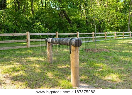 An empty hitching post is by a bridle path